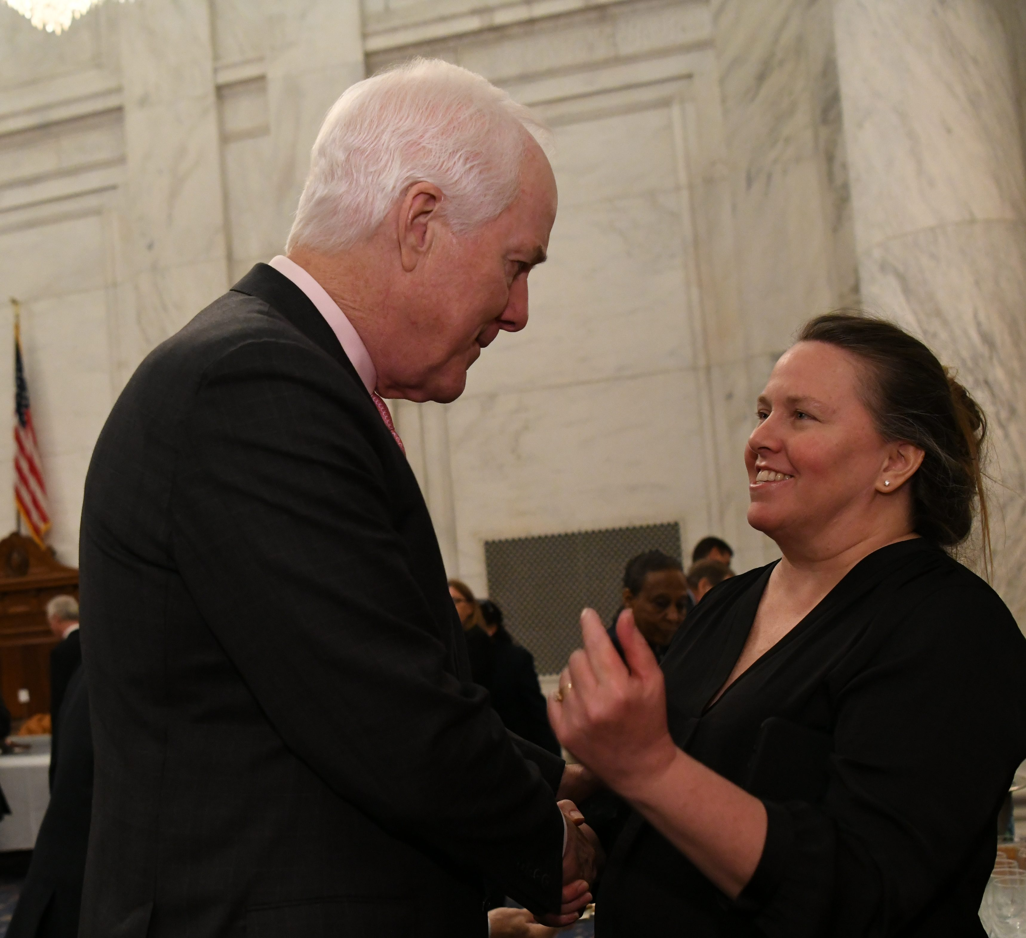 Texas Senator John Cornyn (left) welcomes Monica Heil (right), who is the administrative director for Senator Isakson, into the Kennedy Caucus Room during the luncheon. Monica and family hosted the South 40 Smokehouse catering team into their home where all of the food was prepared in their driveway using several different pits and catering trailer.